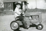 Smith Freeman rides his toy tractor in this undated family photograph. Not long after the death of...