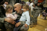 Carlessa Schulz, cq, far left, with daughters Brilynn, cq, 1, and Breann, cq, 3, greet Spc. Eric...