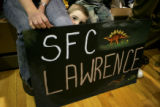 Ashton Lawrence, cq, 2, peeks from behind a sign made to welcome his father, SFC Anthony Lawrence,...