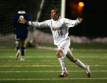 Arapahoe High School's Joe Madigan (#16, For) runs towards the bench and his home crowd while...