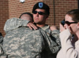 SGT Marcus Averill, cq, hugs fellow soldier, SPC Robert Themel, his wife Dana Averill, cq, gets...