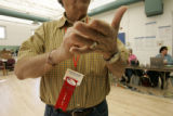 (BG963) Election supervisor Frank Lujan, 78, wears an Habla Espanol ribbon to let people know if...
