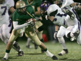 Mountain Vista's Adam Paranka, left, gets brought down by Douglas County's Luke Diehl, right, in...