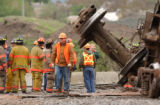 [Denver, CO - Shot on: 5/14/04]  Railroad workers and fire fighters inspect an accident that left...