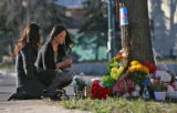 Sisters Nga Nguyen, left, and Samantha Nguyen set out burning incense at a memorial for their...