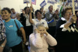 Juanita Swanson (cq) (l) holds her ears to protect them from the crowd's roar during a Democratic...