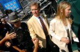 (CANTON, Ohio., SHOT 8/8/2004) John Elway (center) shakes hands with a fan as he and his 18...