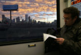 (DLM5835) -  The city skyline looms in the background as Steve Obrand reads while taking a light...