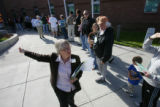 Poll watcher Paula Vandusen (Cq), tells voters about other voting centers that they could go to...