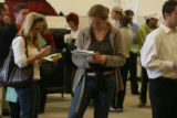Amy Telligman (cq) ,right, reads a book while waiting in line with other  Election Day voters at...