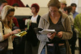 Amy Telligman (cq) ,right, reads a book while waiting with other  Election Day voters at the...