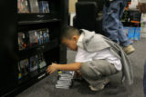 Tommy Nguyen, 8, of Denver scans through a selection of discounted DVDs as he hope to take...
