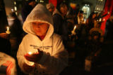 Chris Little Son, 11 of Lame Deer, MT., shields his candle, Friday Nov. 24, 2006 during a vigil of...