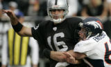 (BG0320} Denver Broncos John Engelberger, right, hits Oakland Raiders QB Andrew Walter in the...
