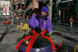 Dean Garcia fixes ribbons on Christmas decorations before it is hung on the 16th Street Mall...