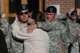 Sgt. Marcus Averill, cq, receives a kiss from his wife Dana Averill, cq, after he exits the...