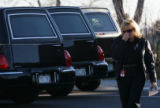 (DLM3991) -  A woman who asked to remain unidentified walks past the row of hearses parked outside...