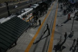 (DLM4922) -  A man on stilts crosses the tracks at the Lincoln Avenue Light Rail Station as the...