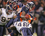[ES222] - Denver Bronco running back Mike Bell avoids the grip of San Diego defenders Ryon...