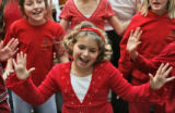 Andi Owens, 9, performs along with the rest of the choir from Beacon County Day School, as they...