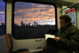 (DLM5832) -  The city skyline looms in the background as Steve Obrand reads while taking a light...