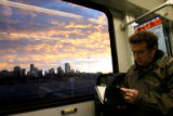 (DLM5838) -  The city skyline looms in the background as Steve Obrand reads while taking a light...