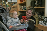 Gretchen DeWolfe, (cq - right) plays with a rattle with her one year old daughter Katherine...