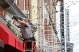 Mike Weber, (cq), measures and helps install strings of lights on the street. Larimer Square,...