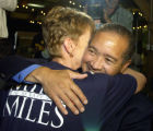 (DENVER, Colorado. August 10, 2004) Mike Miles is hugged by one of his wife Karen as he arrives at...