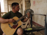 copy of photo of Joe Kaniatobe (cq) playing his guitar while on duty in Ramadi, Iraq. His mother...