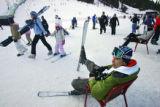 Vito Zigic (cq, in chair), 27, of Chicago, Ill. sits in a chair with his skis on while waiting for...
