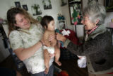 Volunteer Polly Phillips  (r), from Evergreen, gives a toy to Dominique Rodriguez, 6 months, after...