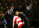 MJM282   Heidi Anderson, center, kisses the coffin of her boyfriend, Colorado Springs officer Ken...