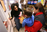 MJM121  Emergency Family Assistance Association volunteer, Kerry Kity (cq), left, helps Raquel...