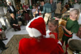 (DLM1555) -  Cassidy Bucholz, 8, sits on Santa's lap during the annual lighting of the tree...
