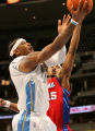 MJM146   Carmelo Anthony of the Denver Nuggets goes in for a lay up as he is defended by James...