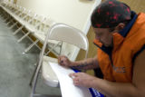 DLM0175  Andrew Gomez, 48, of Denver uses a chair as a desk to fill out paperwork after coming...