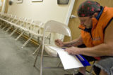 DLM0176  Andrew Gomez, 48, of Denver uses a chair as a desk to fill out paperwork after coming...