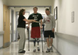Tyler Carron (cq), walks with the help of his physical therapist Sylvia Boedeker (cq) and his...
