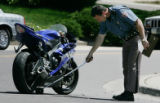 JOE328 Colorado State Patrol trooper T.C. Kridel (cq) makes a measurement next to a Yamaha R6...