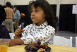 Tiffany Nuckolls, (from mom), 5, waits patiently with her mom having fresh strawberries as they...