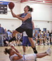 Ashley Tanner (with ball) from the  Cheyenne River Reservation in S.D.  takes a blocking foul as...