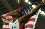 American long jumper Dwight Phillips carries a United States flag around Olympic Stadium after...