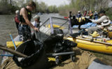 Jason Uhlman left, hauls a shopping cart they pulled out of the river at a pull out  at the...
