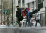 sPedestrian fight the rain and wind while crossing Arapaho Steet in Denver, Colo., on Tuesday,...