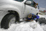 Karla Balk tries to get at the concrete like snow under her car while her dog Disa hangs out the...