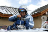 Kathy Kuwahara (cq), of Thorton, adjusts her snowboard after making a run Wednesday morning, April...