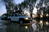 DLM0157  Water surrounds Marilyn Hilzer, 61, as she sits on the tailgate of her pick-up at 11056...