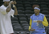 Denver Nuggets teammates Allen Iverson, left, pulls the head phones out of Carmelo Anthony's iPod...