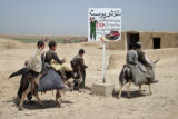 "HMD101 - Afghan boys ride donkeys as they pass by a sign reading: ""Check point search""..."